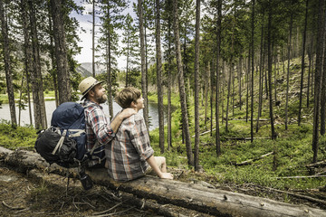 Father with arm around son sitting on fallen tree in forest, looking away, Red Lodge, Montana, USA