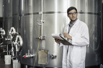 Brewer in brewery wearing lab coat holding clipboard looking away