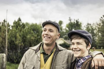 Man wearing flat cap, arm around boy looking away smiling