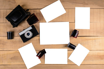 Old film camera and empty white space for photos on a wooden table