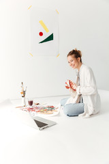 Cheerful young caucasian lady painter at workspace using laptop