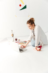 Amazing young caucasian lady painter at workspace using laptop