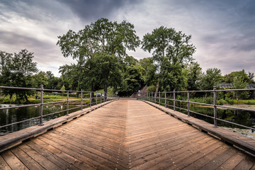 Bridge over pond in Churchill Park in Copenhagen, Denmark, a cloudy day of summer