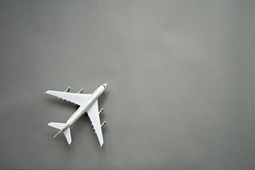 Flat lay design of travel concept with plane on gray background with copy space.