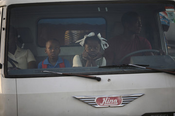 School children commute in the cabin of a truck used as collective transportation in a street of Port-au-Prince