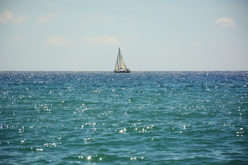 Lonely sailboat in the sea on the horizon, shine and radiance of water