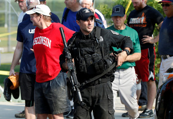 A police officer escorts members of Congress and staff from the scene after a gunman opened fire on members of Congress during baseball practice in Alexandria, Virginia