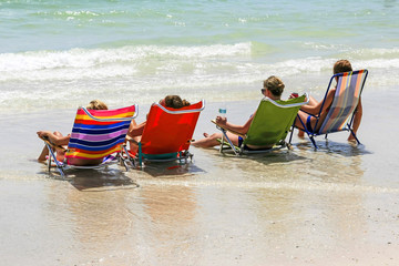 College girls sitting in beach chairs at the waters edge relaxing during summer vacation