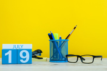 July 19th. Image of july 19, calendar on yellow background with office supplies. Summer time. With empty space for text