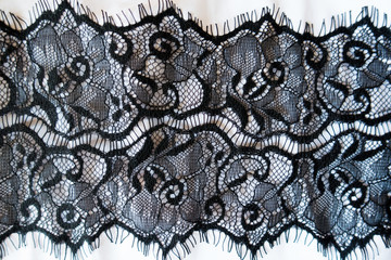 Horizontal ribbon of black guipure over white fabric