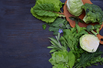 Composition on a dark background of green leafy vegetables containing folic acid, riboflavin, vitamin B9, B2, K, C - cabbage, broccoli, chard, lettuce, spinach, parsley, celery, dill, sage. Top view.