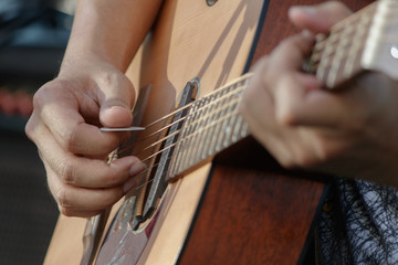 Closeup hand with pick play on acoustic guitar.