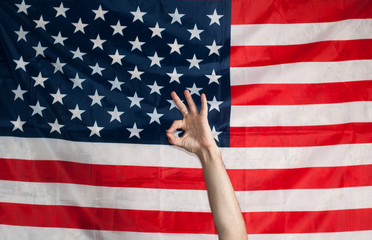 okay on the background of an American flag, a gesture with his hands