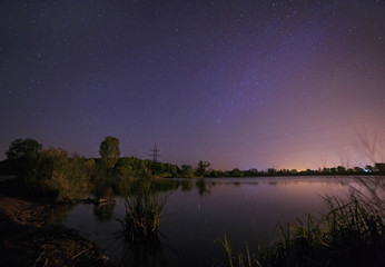 view on starry night sky above lake