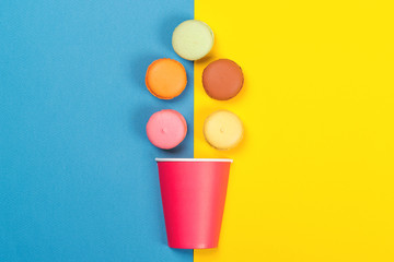 Colorful macaroons falling into red paper cup. Minimal concept. Appetizing macaroons on blue and yellow background.