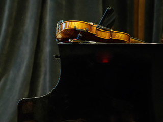 Violin on the grand piano in a concert hall