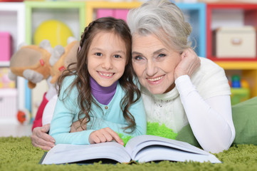 Grandmother reading book with granddaughter