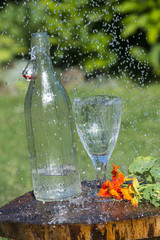 Glass with mineral water in rain