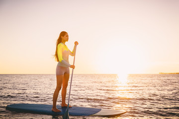Perfect slim woman stand up paddle surfing with beautiful sunset colors