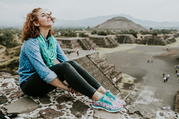 .Young carefree female tourist enjoying the pyramids of Teotihuacan in Mexico. Lifestyle portrait.