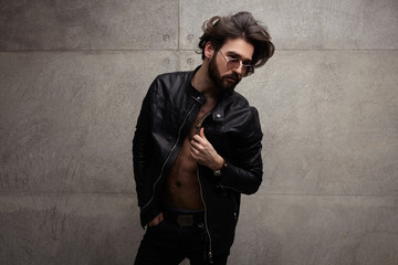 Confident trendy man in leather jacket