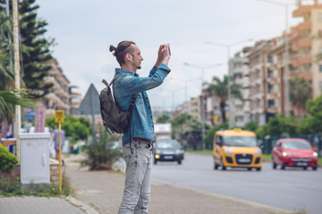 Man traveler with backpack makes a photo on your smartphone on a city street