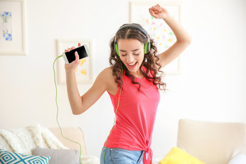 Beautiful young woman in headphones listening to music at home