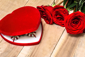 Necklace in a box in the form of a heart lies on a table with red roses