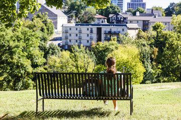 A female University of Tennessee student sits quietly looking at the city of Knoxville from the Hill