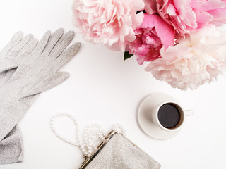 Still life with cup of coffee, peonies flowers and gloves on light table. Flat lay. Top view