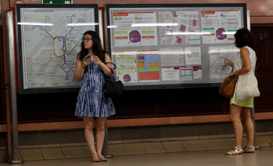 Women stand beside a board showing railway network maps as they wait for a commuter rail at Recoletos train station in Madrid
