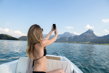 Young woman taking a selfie on a boat