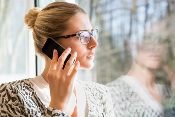 Happy woman in eyeglasses using cell phone