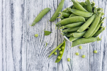 Green peas in white bowl on grey wooden background