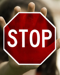 Young Girl Making a Stop Motion with a See-through Red Stop Sign Over her Hand