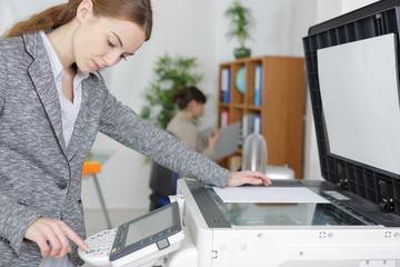 beautiful girl operating copier in modern office