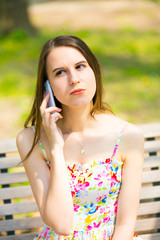 Portrait of young beautiful woman with long hair in summer park, girl wearing flower short dress is using a smartphone while sitting on a bench