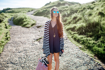 Young woman dressed in hippie style walking with beach bag outdoors