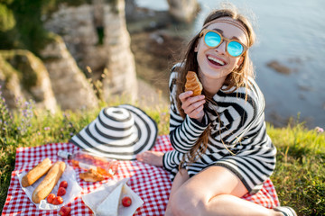 Young woman having a picnic with wine, cheese and bread sitting on the rocky coastline in France