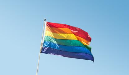 GLBTQ Pride Rainbow Flag on blue sky Right