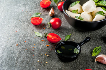 Farm raw organic products. Cooking of dinner in Italian style. Ingredients for caprese salad, pasta, pizza. Basil, tomatoes, mozzarella cheese, olive oil. dark grey stone table. Copy space