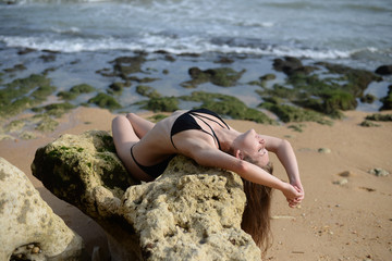 Joyful beach holiday fun. Attractive young, fit and sexy woman in swimsuit on sunny outdoor background