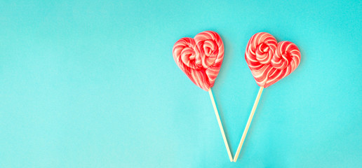 Two red heart shaped lollipops on a vibrant blue background with copy space on left for Valentines card. Valentines Day background