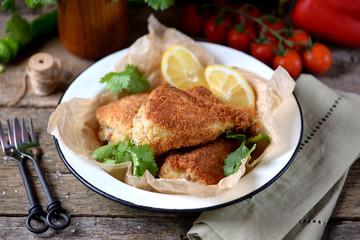 Chicken legs fried in breadcrumbs in deep-fried, rustic style. Old wooden background.