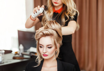 Professional Hairdresser using hair spray on client business woman hair at beauty salon