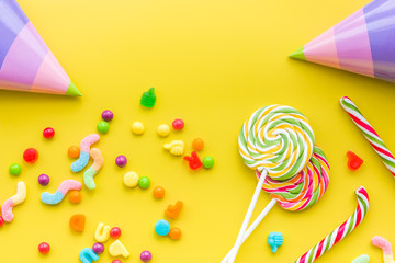 Birthday concept with sweets and party hats on yellow background top view copyspace