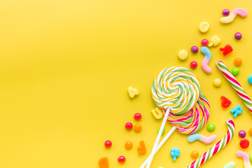 Sweets for birthday including lollipop and drops on yellow background top view copyspace