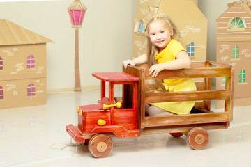 little girl is riding a toy wooden car.