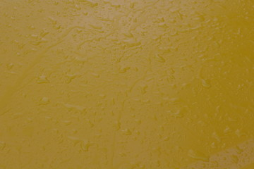 Raindrops on the side of a yellow car