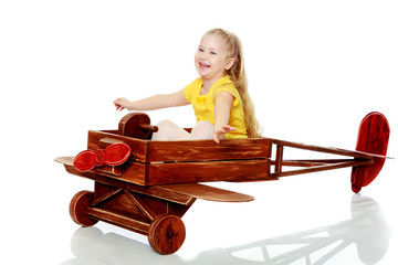 Girl is riding a toy plane.